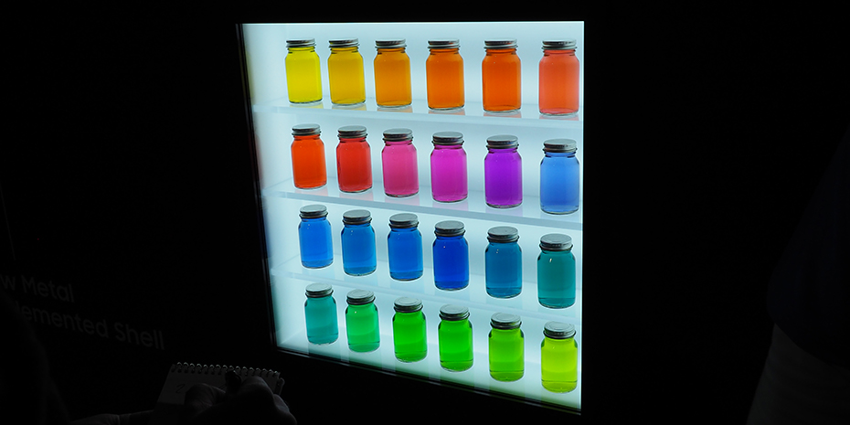 """De här burkarna är fyllda med mikroskopiska partiklar, """"kvantprickar"""", som avger olika färger beroende på hur stora partiklarna är. Ljuset som lyser genom alla burkarna är vitt. Foto: Geir Gråbein Nordby"""